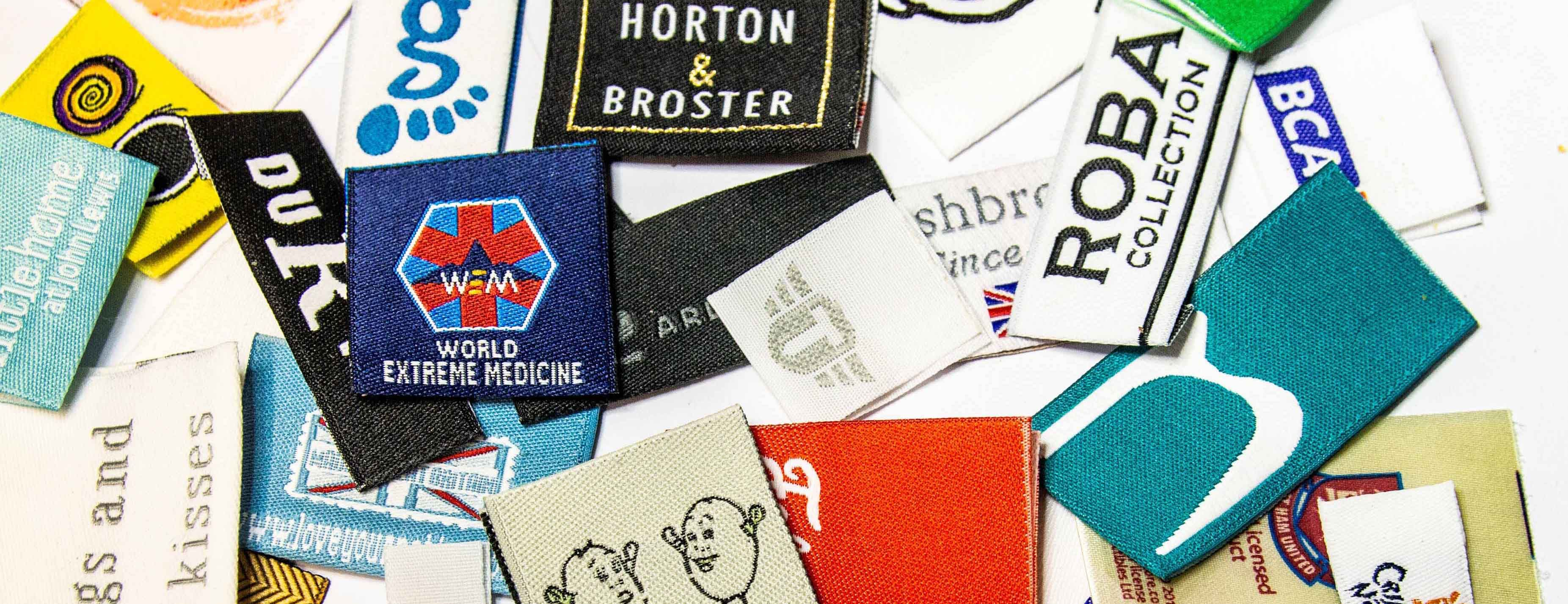 A collectoin of customised woven fabric labels made in the UK.